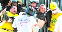 Rescate. Los socorristas no escatimaron esfuerzos para rescatar a los policías heridos. En la gráfica trasladan a un antimotín hacia un centro hospitalario. Foto: EDH